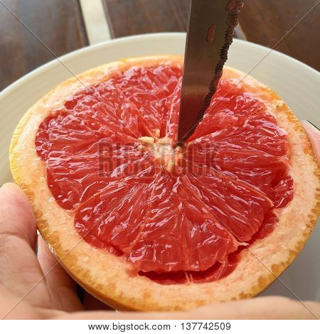 Using a knife to segment a Pink Grapefruit half