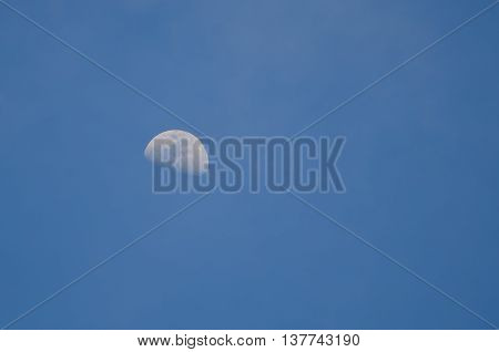 Part of the moon on a background of blue sky