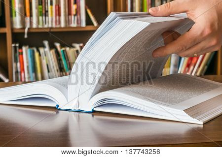 The Hand Opening And Browsing The Book Pages