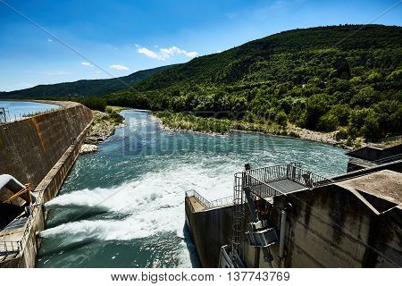Dam of hydroelectric power plant in the mountains. Water rushing through gates at a dam. The dam closeup.