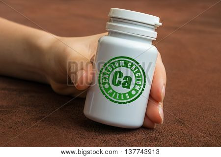 Human Hand Holding A Bottle Of Pills With Calcium
