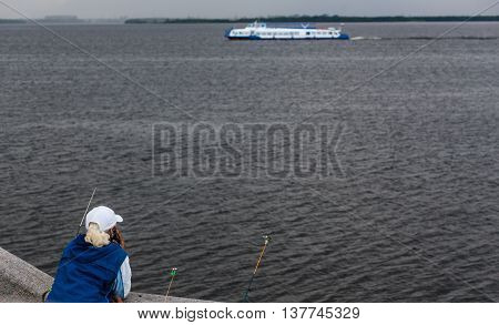 Side view of young man sitting on pier with rodBack view of old fisherman standing on pier with rods and looks afar.