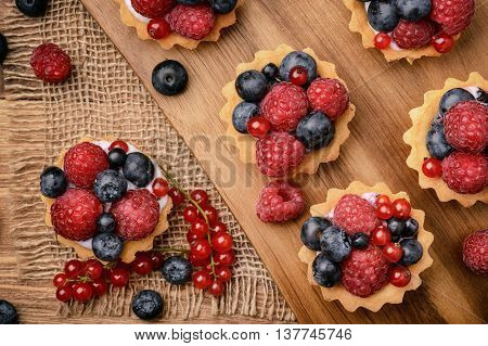 Tartlets with cream, blueberries, raspberries and red currants on brown wooden background. Top view.