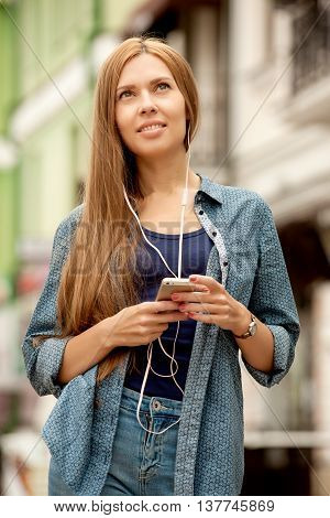 Young stylish woman with headphones and phone listening to music. The girl posing in the city streets. vacation europe