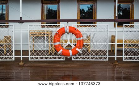 Lifebuoy on a ship railing with deck windows on a background.