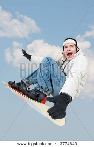 Portrait of young boy with snowboard jumping on the background of sky