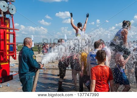 Tyumen, Russia - July 9, 2016: Steel Character extrim race on Voronino Hill. Firefighter pours water from a hose of the wishing athletes after finishing