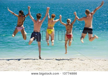 Portrait of five teens jumping into lake simultaneously holding each other by hands