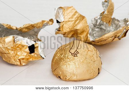 Chocolates in shiny foil deployed on a white background