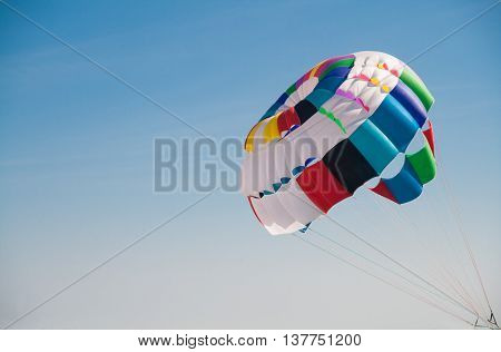 Colorful round parachute against the blue sky