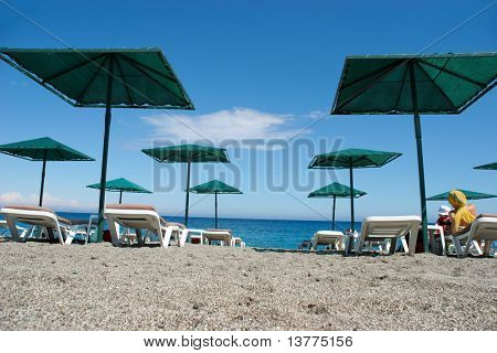 Photo of tourists lying on deck-chairs on seashore with water near by in summer
