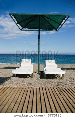 Photo of two deck-chairs with umbrella near by on sandy coast