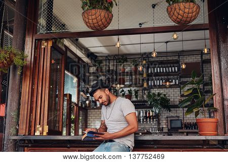 Relaxed Young Man At Cafe Counter Reading A Book