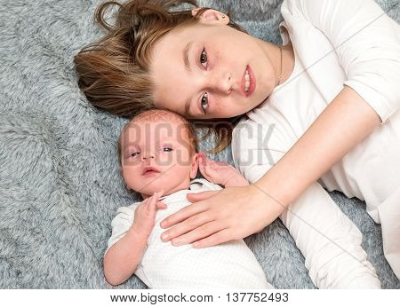 Two Sisters. Older Sister Kid Hugging His Newborn Little Sister.