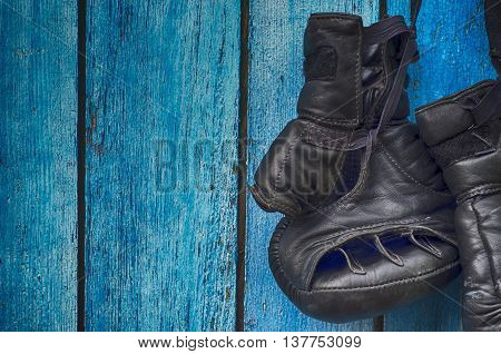 Black gloves for kickboxing hanging on wooden blue wall