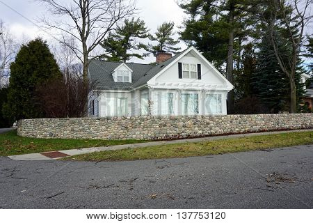 A white home behind a stone wall on East Bluff Drive in Harbor Springs, Michigan.
