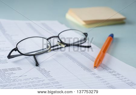 Workplace Accountant. Documents, Pen, Glasses, Paper For Notes. On Paper, The Table Is A List Of Pro