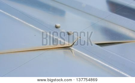 Rooftop aluminum cover with screws detail. Grey industrial cover of the roof. Shiny metal cover of the rooftop. Metallic waves on the roof. Detail of the screws holding metallic roof.