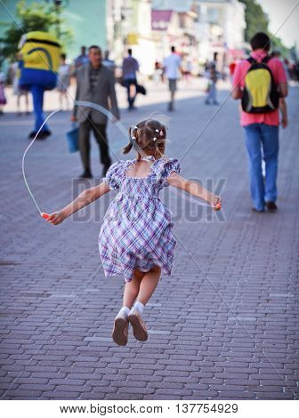 A girl with skipping rope on a street