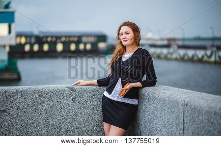 Beautiful girl standing on the bank of the river. She holding phone and looking afar