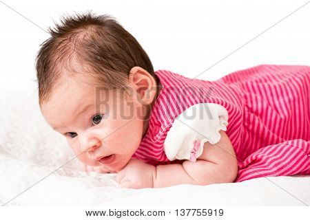 Newborn baby girl with open keen eyes laying in his bed with white background