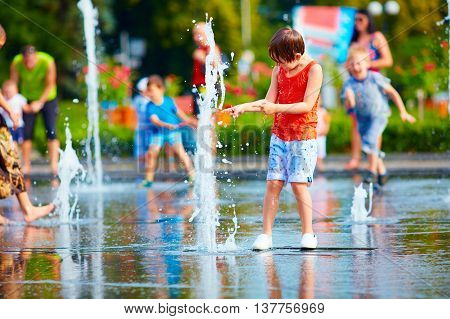 Excited Boy Having Fun Between Water Splashes, In Fountain. Summer In The City