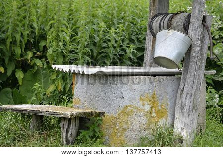 close-up of an old well with wooden beams on which hangs a bucket and mug