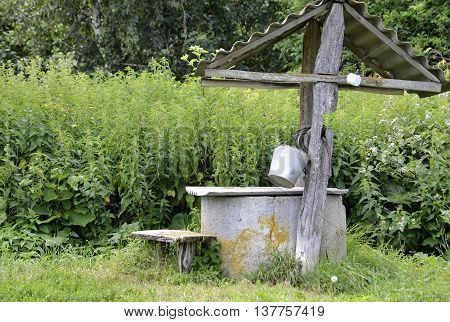 old well with wooden beams on which hangs a bucket and mug