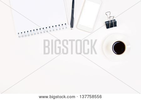 Top view of bright office desktop with blank white smartphone notepad coffee cup and other stationery items. Mock up