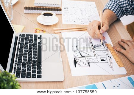 Young architect using ruler and pencil to draw construction sketch on wooden office desktop with blank laptop coffee cup business report and stationery items. Mock up