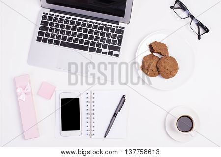 Top view of light girly office desktop with blank smart phone glasses laptop keyboard coffee cup gift case cookies on plate and other items. Mock up