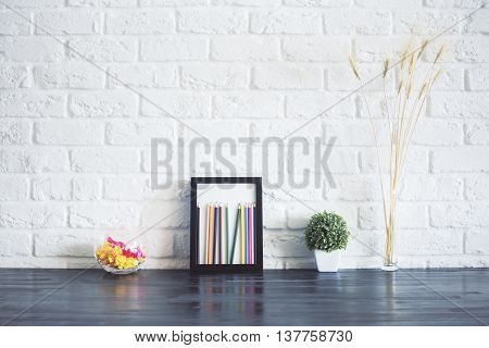 Front view of dark wooden surface with wheat spikes plant colorful pencils inside picture frame and glass bowl with crumpled paper on white brick background
