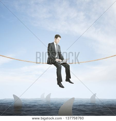 Risk concept with businessman using laptop on rope above sea full of sharks on sky background