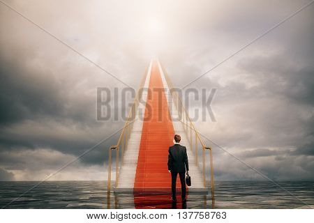 Success concept with businessman climbing concrete stairs in the sky.