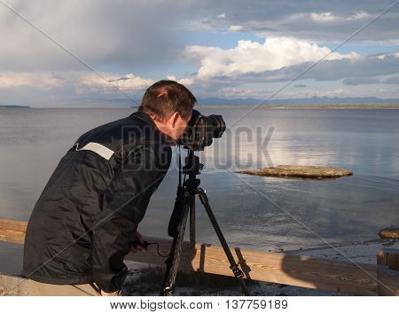 Photographer taking photo of lake with camera in tripod