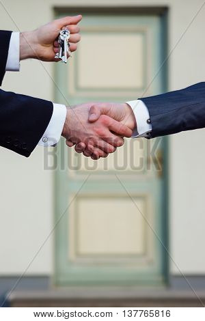 Succesful handshake of customer and buyer and keys from a real estate
