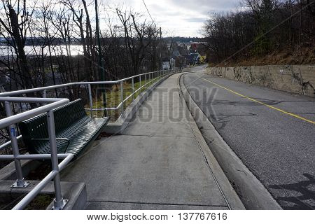 HARBOR SPRINGS, MICHIGAN / UNITED STATES - DECEMBER 25, 2015: A bench is available for people to rest who are walking to the top of the bluff in Harbor Springs, Michigan, via the steep incline of Judd Hill (Arbor Street).