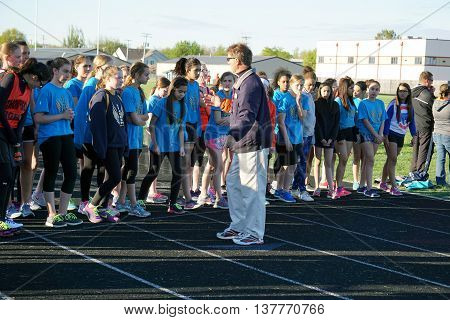 OSWEGO, ILLINOIS / UNITED STATES - MAY 2, 2016: Eighth grade girls, from Drauden Point and Thompson Middle Schools, prepare to run the 400 meter dash at Oswego High School's Ken Pickerill Stadium.
