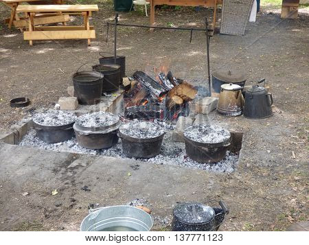 An outdoor wood fire pit used for cooking and baking food in cast iron pots and pans.