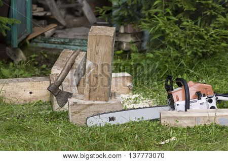 A chainsaw and an ax next to the woods laying on the grass in the backyard selective focus outdoor shot