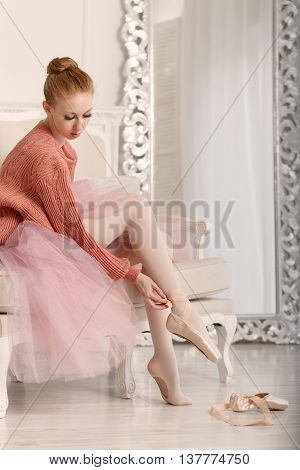 Pretty young ballerina puts on pointe. Ballerina in tutu and pink sweater