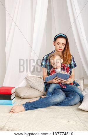 Young mother and baby daughter hugging sitting on the floor. Mother and daughter reading a book. Girls dressed in plaid shirt. Family education