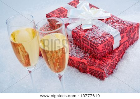 Close-up of red giftboxes with two flutes of champagne near by