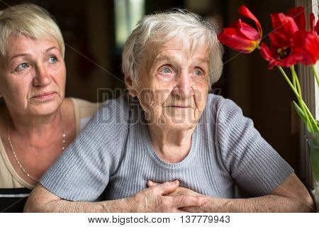 Pensive elderly woman portrait, with the adult daughter in the background.
