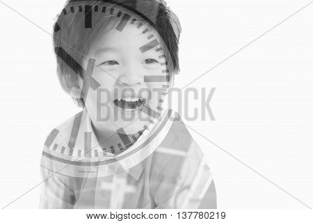 Double exposure of asian boy combined with photograph of a clock at a train station