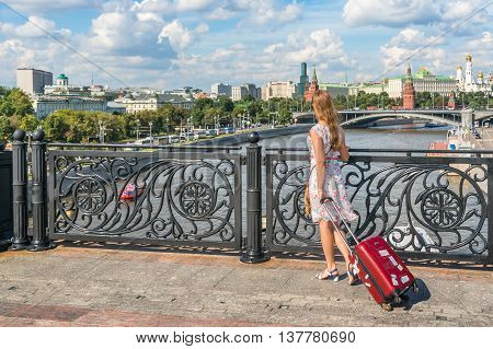 Young Woman Walking And Carrying A Suitcase In Moscow