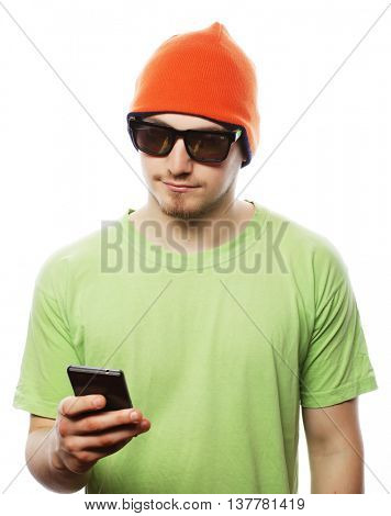 life style, tehnology and people concept: cheerful man in green shirt and bright hat using smartphone, isolated on white