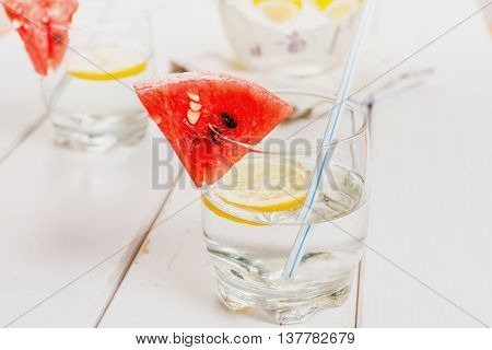 Fresh water with lemon and melon on white wood table