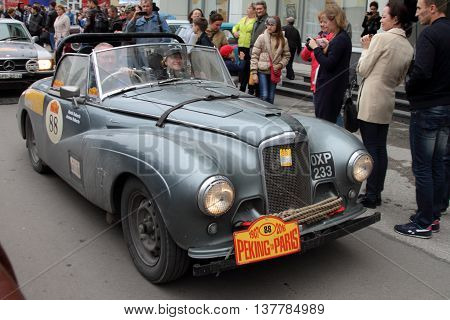 PERM RUSSIA - JUNE 29 2016: Rally of retro-cars Peking-Paris 2016 June 29 2016 in Perm Russia. The inhabitants of the city greeted the car Sunbeam Alpine participating in the rally.