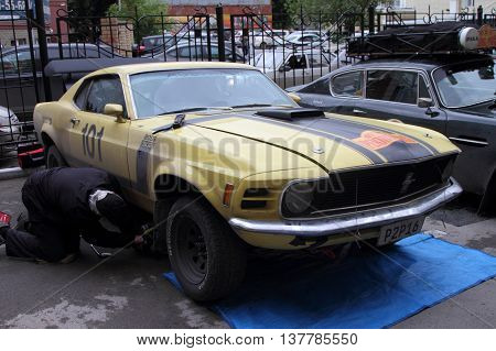 PERM RUSSIA - JUNE 29 2016: Rally of retro-cars Peking-Paris 2016 June 29 2016 in Perm Russia. Member of the rally repairing the car Ford Mustang.